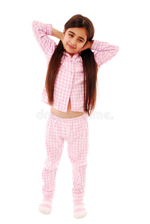 Morning. Cute little girl stretching wearing pajamas isolated on white stock photos
