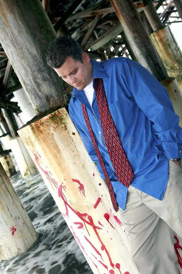 Morning After. Businessman contemplates his future under a seaside pier royalty free stock images