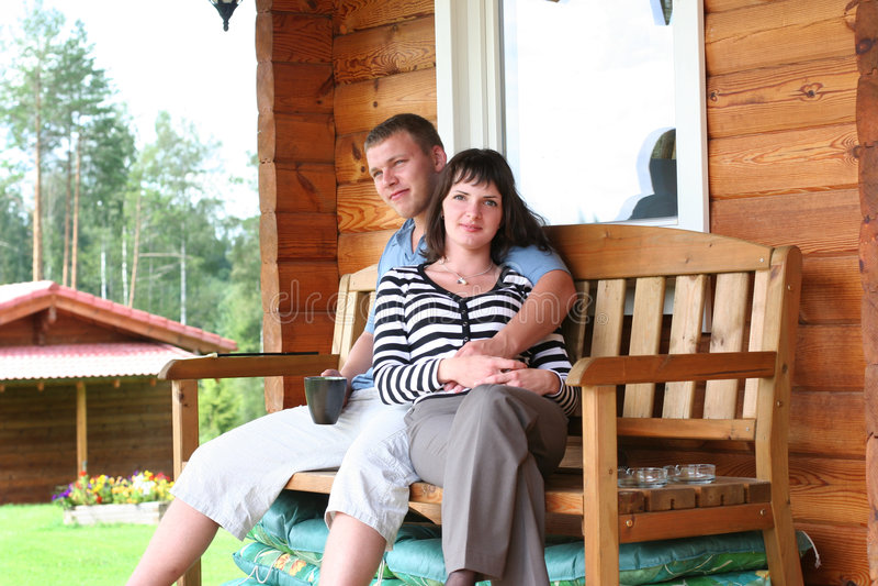 Morning. Young couple drinking tea on verandah royalty free stock image