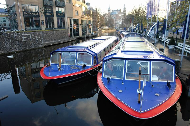 Morning in Amsterdam. Water street with boats on the pier, reflected in quiet water. stock photos