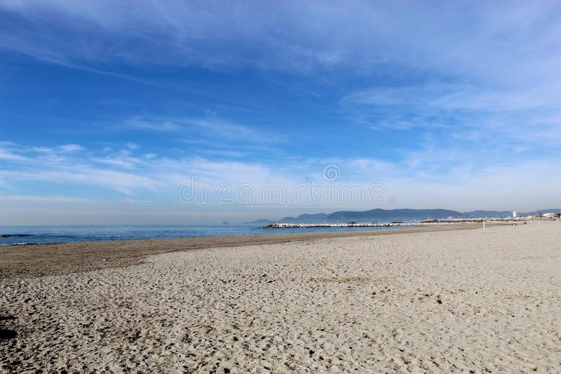 A sunny thursday morning at the beach in Marina di Massa in Italy. In the morning at the beach. The sun was shining bit it was cold. Birds were sitting on the royalty free stock photography