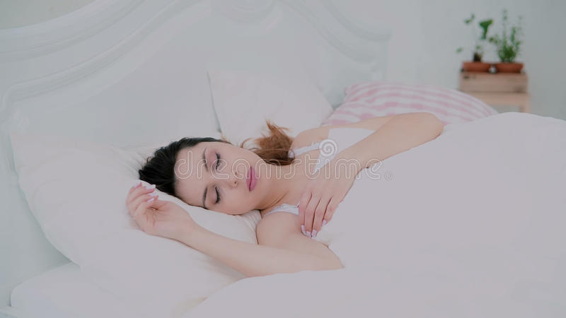 Morning of beautiful girl in light apartments. Young woman lying in bed, waking up and smile. Female looking at camera. stock photos