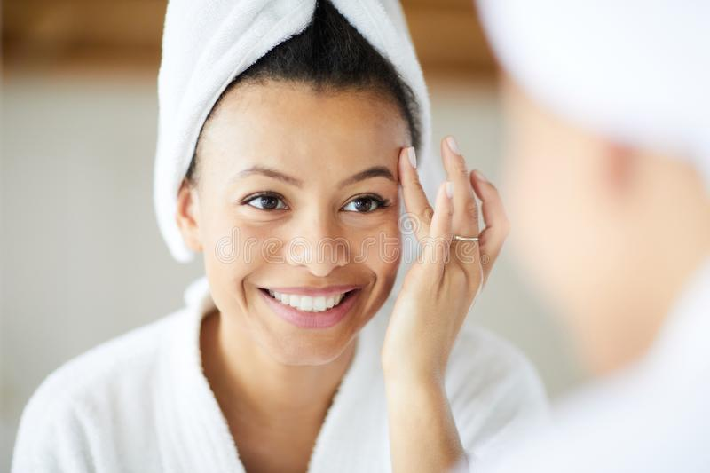 Morning Beauty Routine. Head and shoulders portrait of  smiling Mixed-Race woman applying face cream during morning routine, copy space stock photography