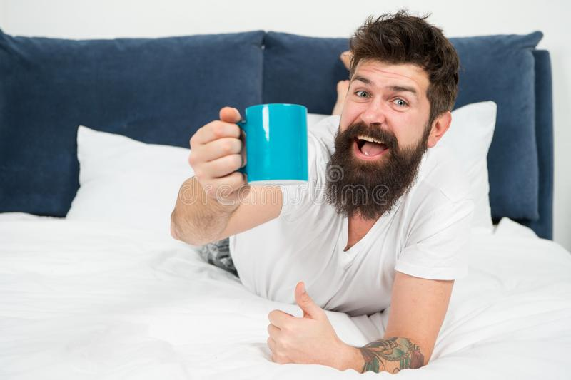 Morning becomes much better with good coffee. Relax and rest. Full of energy. Coffee affects body. Man handsome hipster. Relaxing on bed with coffee cup stock images