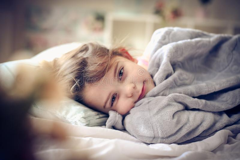 Morning in bed. Little girl lying in bed. Space for copy royalty free stock images