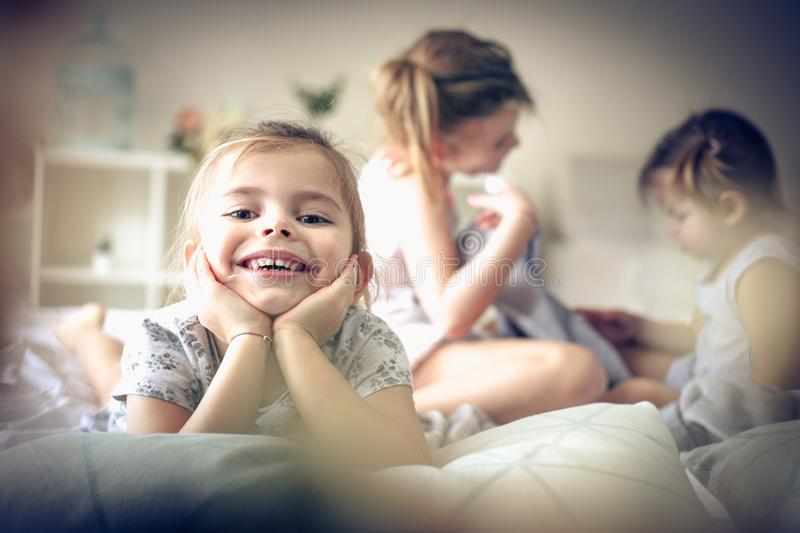 Morning in bed. Three little girls playing in bed. Focus is on little girl. Space for copy stock image