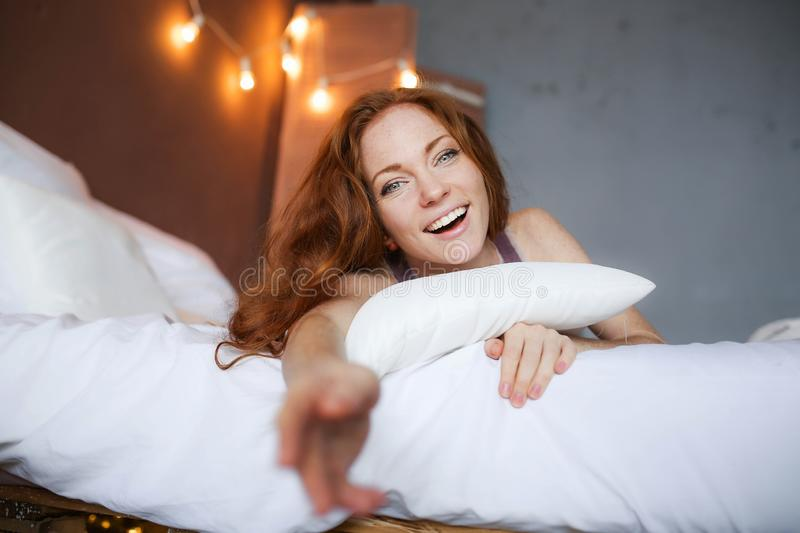 Morning in bed, a young charming red-haired woman with freckles lying in bed, hugging pillow, smiling, enjoying the stock images