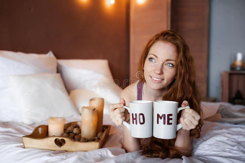 Morning in bed, a young charming red-haired woman with freckles lying in bed, hugging pillow, smiling, enjoying the royalty free stock photo