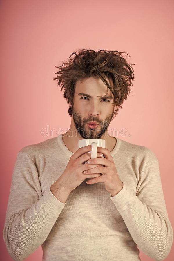 Morning begins with coffee. Morning with coffee or milk. Sleepy guy with tea cup on pink background. Cold and flu, single. Insomnia, refreshment and energy stock photography