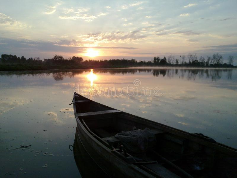 Morning Boat in Sunrise Iran, Gilan, Rasht. Orange canoe outdoor travel clouds riverside sky landscape nature view reflection lake summer fishing color sunset royalty free stock photo