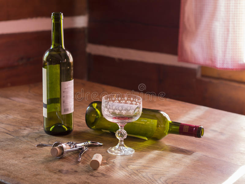 Morning after booze-up two empty bottles of red wine and glass t stock photography