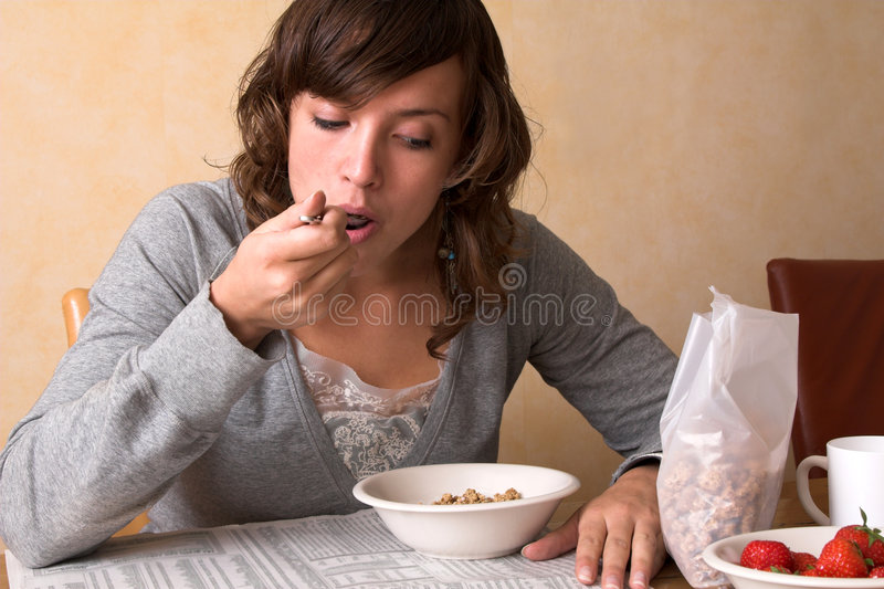 Morning breakfast. Pretty young woman having breakfast while reading the financial newspaper stock photography