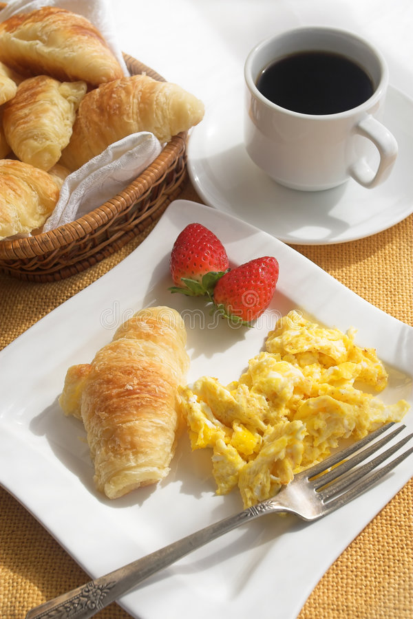 Morning breakfast. Breakfast with scrambled eggs, croissants and a cup of coffee