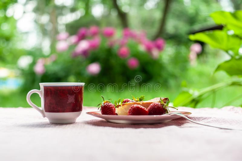 Morning breakfast as of cheese cake, several strawberries on simple plate and 1 white-red cup of coffee on the soft pink. Morning breakfast as of cheese cake royalty free stock images