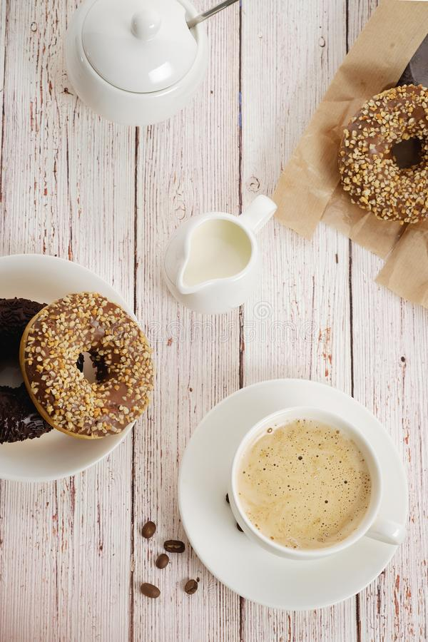 On a light wooden background morning Breakfast, a Cup of coffee with milk and donuts with chocolate. Vertical, top view. royalty free stock photos