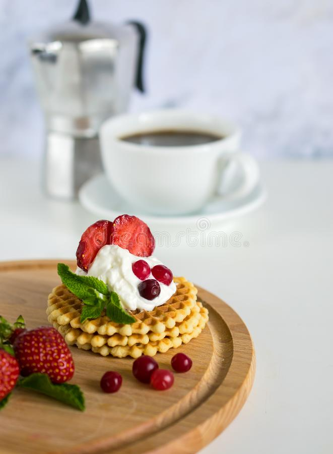 Morning breakfast with coffee and crispy belgian waffles with whipped cream and strawberries. Morning delicious breakfast with coffee and crispy belgian waffles stock photos