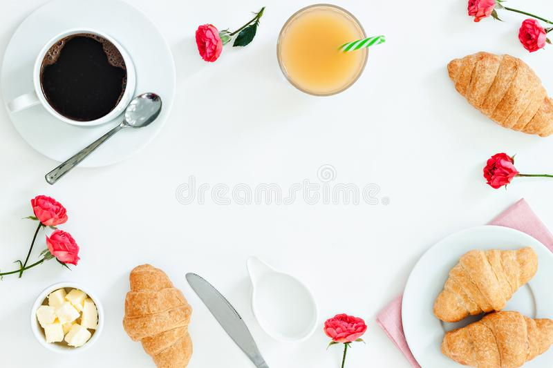 Morning breakfast coffee and croissant, butter, orange juice and flowers on white background. Flat lay royalty free stock images