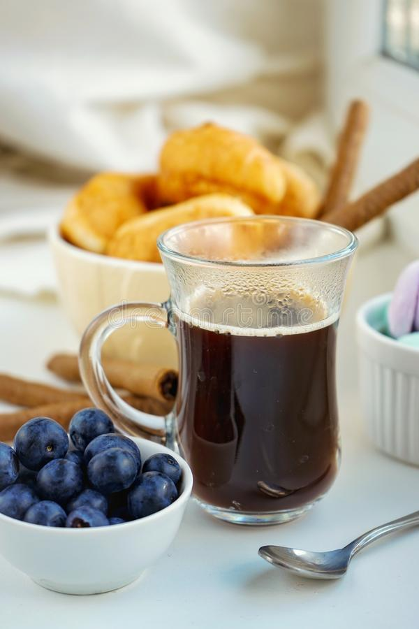 Morning Breakfast Cup of coffee, croissants, colored sweet meringues, blueberries in a clay white glass. Morning breakfast cup coffee croissants colored sweet royalty free stock image