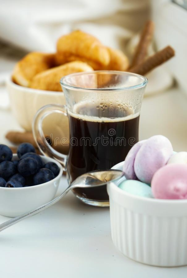 Morning Breakfast Cup of coffee, croissants, colored sweet meringues, blueberries in a clay white glass. Morning breakfast cup coffee croissants colored sweet stock photography