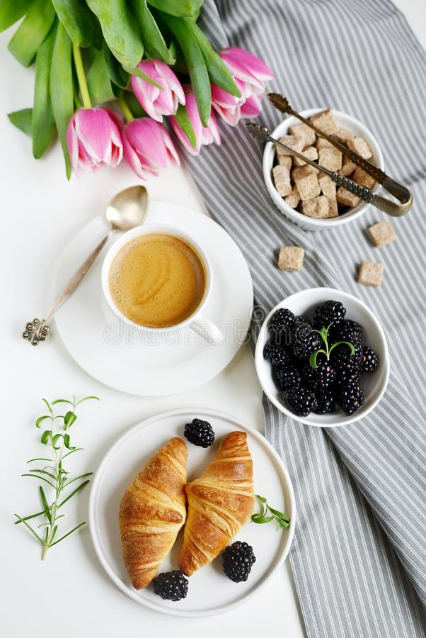 Morning breakfast with cup of coffee, croissants, fresh berries and pink flowers tulips royalty free stock photos