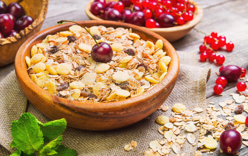 Morning breakfast of muesli. Morning breakfast muesli mix of cereals, dried fruits, berries in bowl. Fresh red berries to muesli cereals cherries, gooseberries stock photography