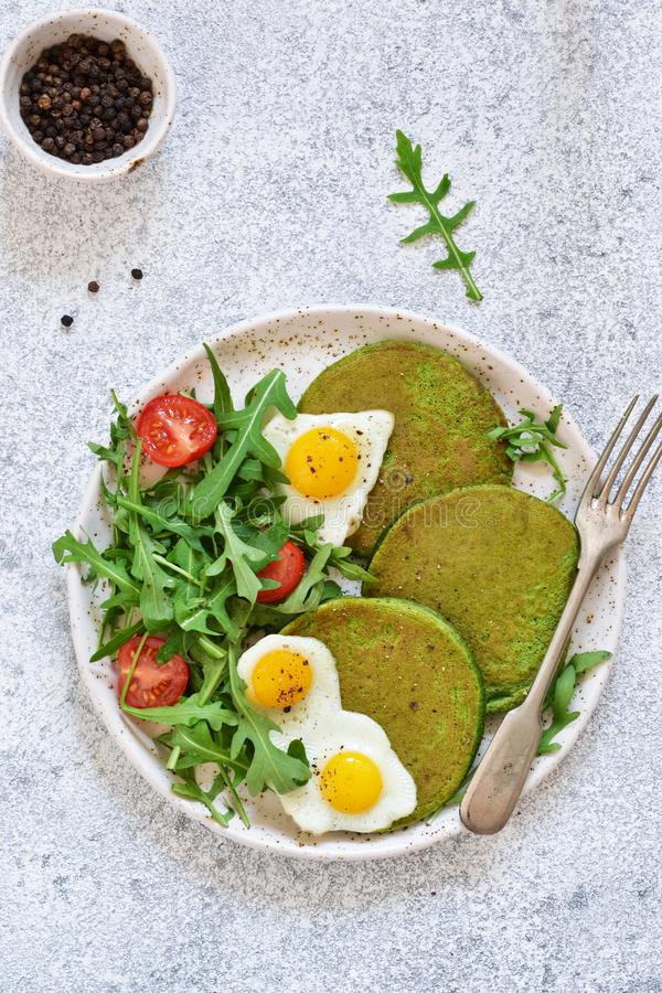 Morning breakfast: pancakes with spinach, salad and egg on the kitchen table. royalty free stock photography