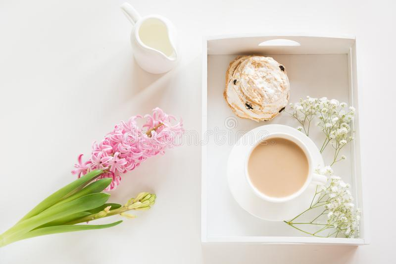 Morning breakfast in spring with a cup of black coffee with milk and pastries in the pastel colors, a bouquet of fresh pink hyacin royalty free stock images