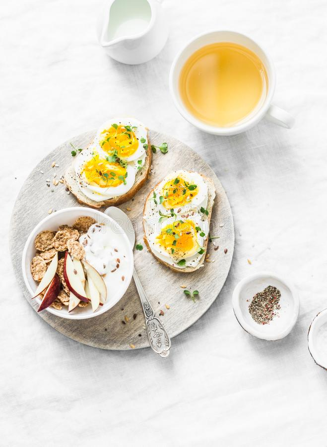 Morning breakfast table inspiration - sandwiches with cream cheese and boiled egg, yogurt with apple and flax seeds, herbal detox. Tea on light background, top stock images