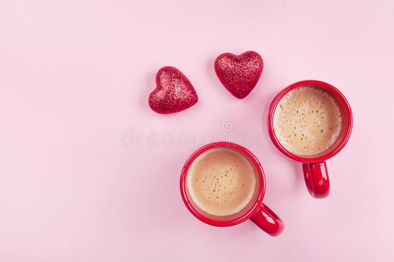 Morning breakfast for Valentines day. Two cups of coffee and red hearts on pink background top view. Flat lay royalty free stock photo