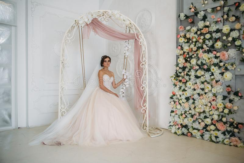 Morning of the bride. Portrait of beautiful woman in white luxury wedding dress with bridal makeup and hairstyle. Amazing model wear diamond jewelry in her stock photography
