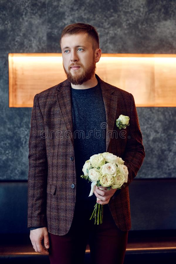 Morning bridegroom. A hipster man in a jacket holding a bouquet of flowers for his beloved. Beautiful bearded man preparing for royalty free stock photography