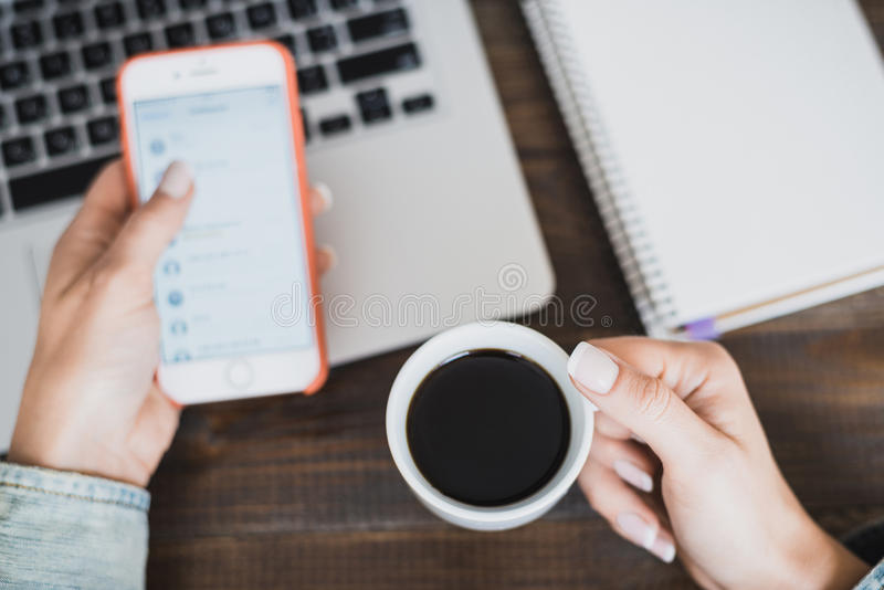 Morning business woman. Laptop on the desk, phone and a cup of coffee in female hands. Horizontal frame stock photography