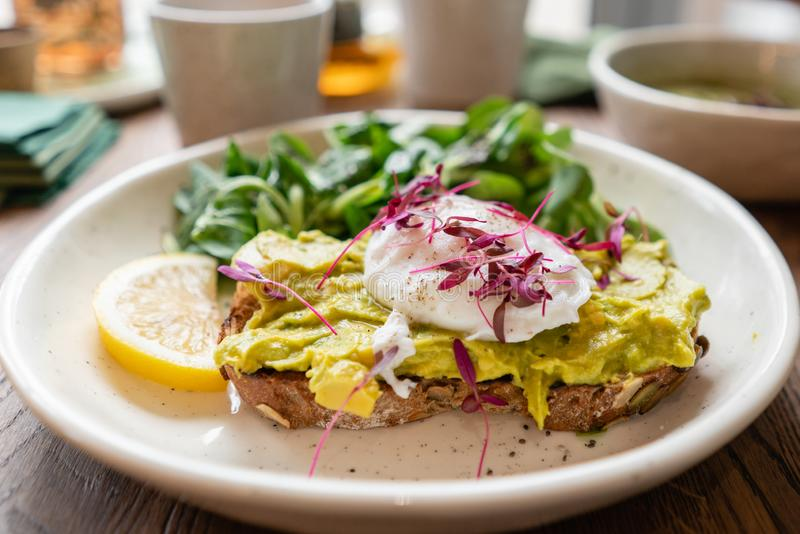 Morning in cafe, oak table. Healthy breakfast with wholemeal bread toast with avocado, poached egg with green salad stock photos