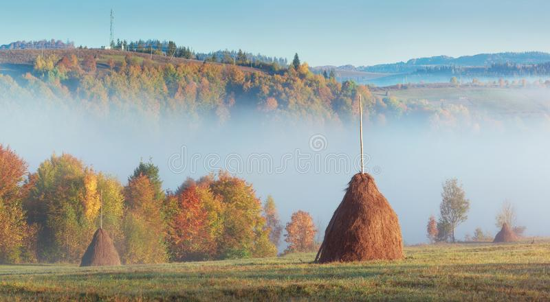 Morning Carpathian hills with fog and haystacks. royalty free stock photos