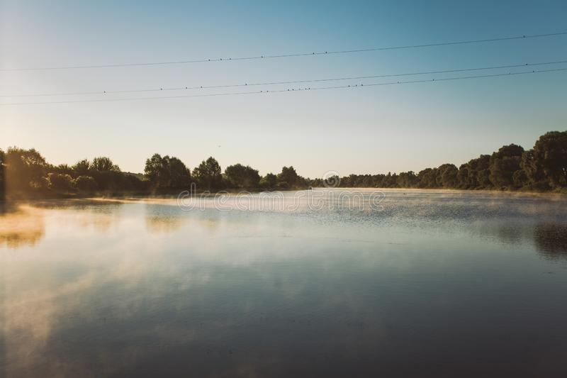 Morning charming sunny fog over calm surface of river water royalty free stock photo