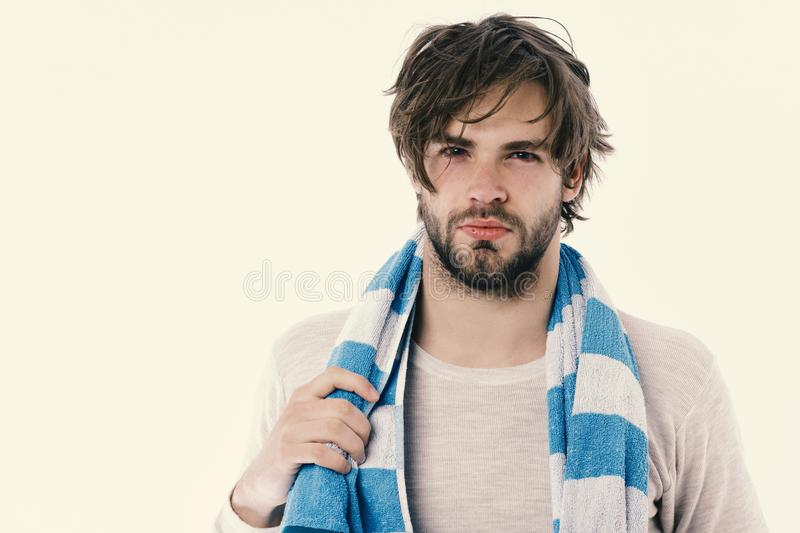 Morning and cleaning concept. Guy with messy hair on white background, copy space. Man with concentrated face wears striped blue and white towel. Macho with stock photography