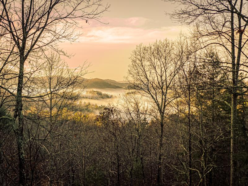 Morning Clouds Above and Below in the Smokies. Winter landscape in the Great Smoky Mountains at dawn with clouds settling in the valley below and the pastel sky royalty free stock photos