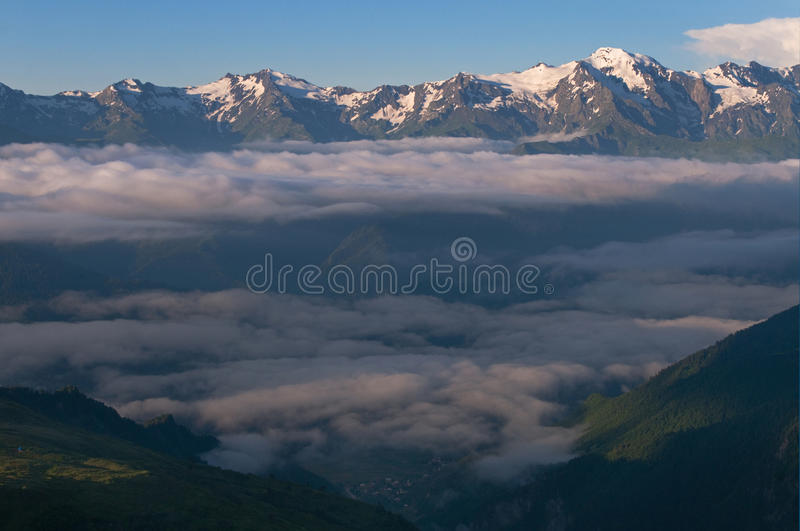 Morning clouds in mountains. Morning: clouds separate into layers. This is Caucasus mountains, Georgia, Mestia royalty free stock image