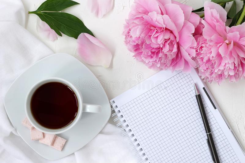 Morning coffee cup and notepad in bright colours with pink flowers royalty free stock images