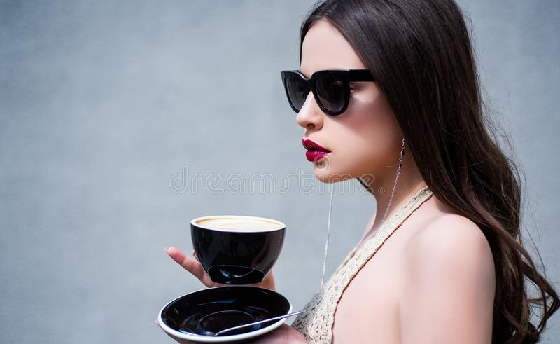 Morning coffee. Beautiful fashion model posing in glasses. Beauty trends. Female fashion model posing with cup. Young royalty free stock image