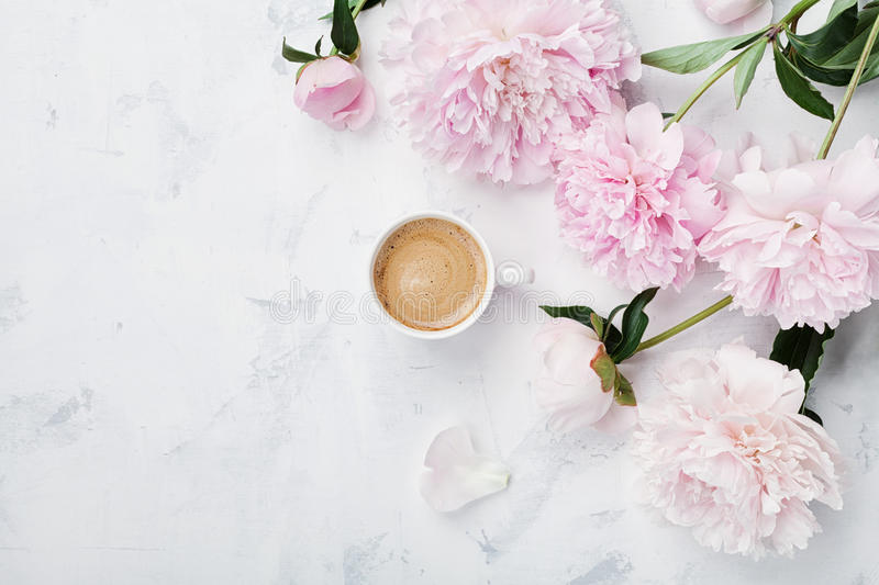 Morning coffee and beautiful pink peony flowers on white stone table top view in flat lay style. Cozy breakfast on Mother day. royalty free stock photo