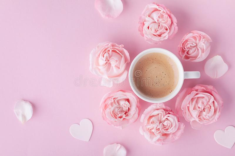 Morning coffee and beautiful rose flowers on pink pastel table top view. Cozy breakfast for Womens or Valentines day. Flat lay. Style stock photo