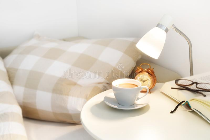 Morning coffee on the bedside table, plus an alarm clock, lamp a royalty free stock photography