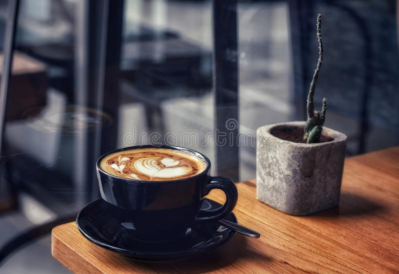 Morning coffee in a black cup on wooden table. Barista, new, window, light, shadow, elements, simple, tasty, taste, yummy, beverage, liquid, caffeine, food stock photos