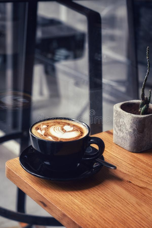 Morning coffee in a black cup on wooden table. Barista, new, window, light, shadow, elements, simple, tasty, taste, yummy, beverage, liquid, caffeine, food royalty free stock photo
