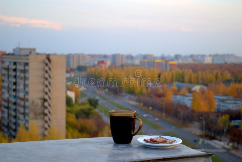Morning coffee with chocolate overlooking the morning autumn panorama of the city. Morning coffee with chocolate overlooking the morning autumn panorama of the royalty free stock images