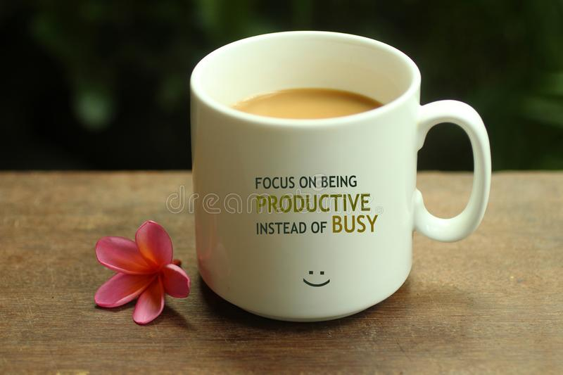 Morning Coffee concept. Work inspirational quote on a mug - Focus on being productive instead of busy. With white mug of coffee stock photos