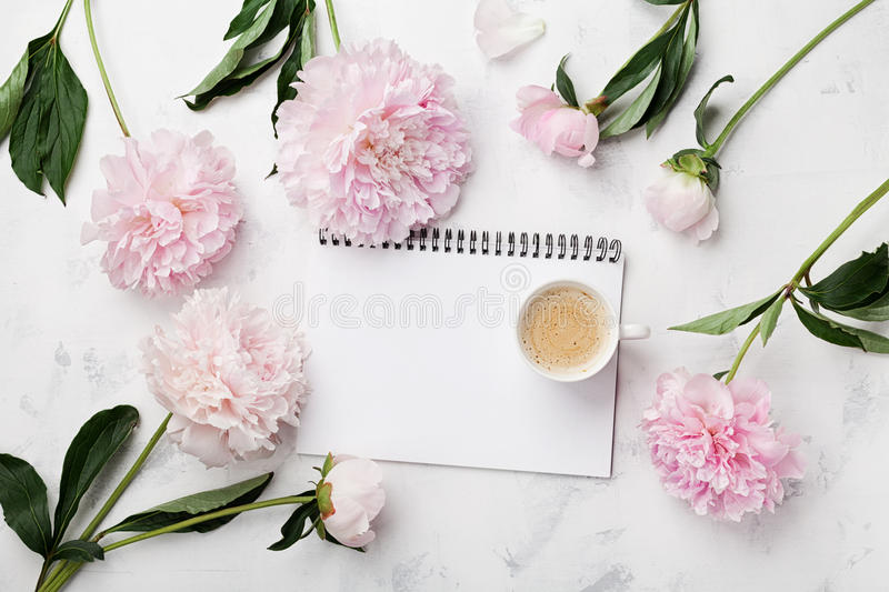 Morning coffee cup for breakfast, empty notebook and pink peony flowers on white stone table top view in flat lay style. Woman working desk royalty free stock photography