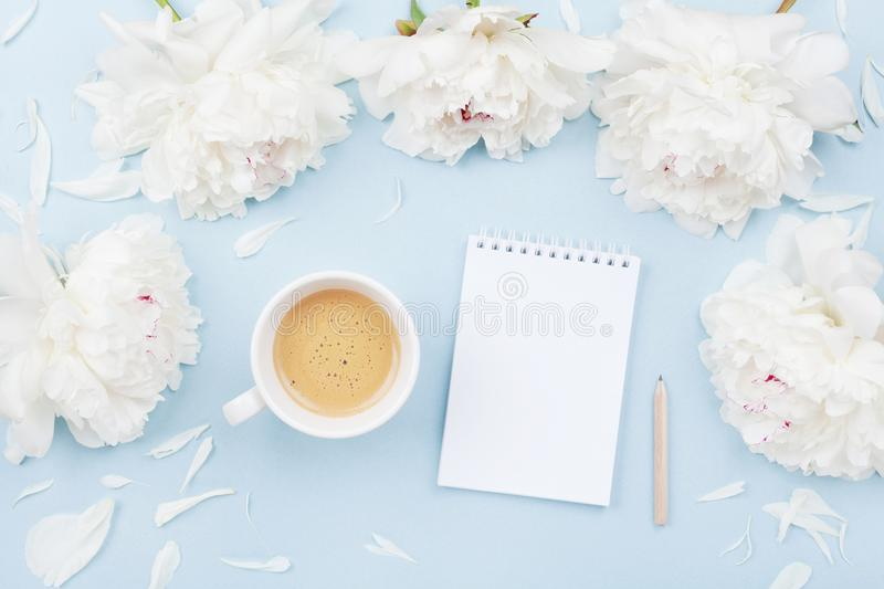 Morning coffee cup for breakfast, empty notebook and white peony flowers on pastel table top view. Woman working desk. Flat lay. Morning coffee cup for stock image