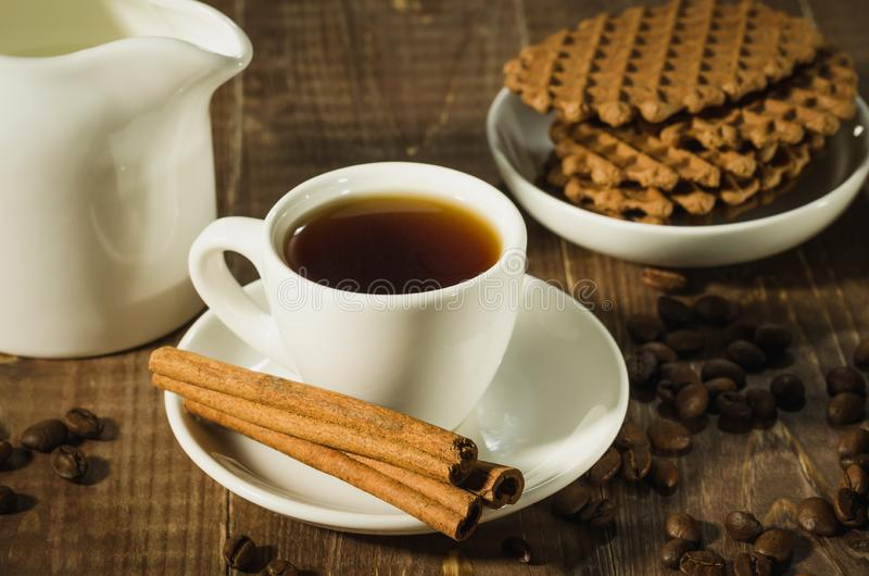 morning coffee cup with cinnamon the scattered coffee beans and cookies/morning coffee cup with cinnamon the scattered coffee royalty free stock photography